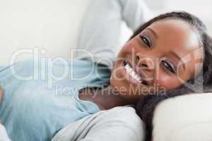 Close up of smiling woman taking a rest on the sofa