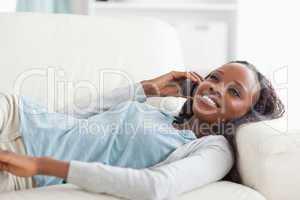 Woman lying on sofa with phone