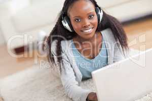 Close up of woman lying on the floor with her laptop enjoying mu