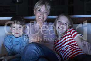 Mother And Children Watching Programme On TV Sitting On Sofa Tog