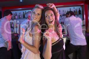 Two Young Women Having Fun In Busy Bar