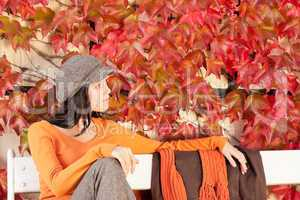 Autumn fashion young woman relax on bench