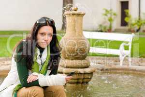 Autumn park fountain young woman hold phone