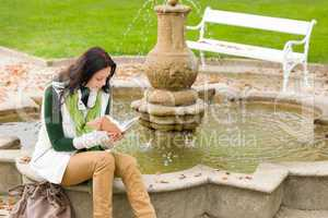 Autumn park fountain young woman read book
