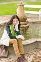 Autumn park young woman sit on fountain