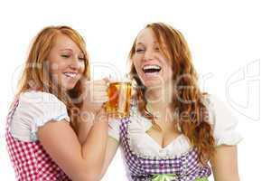 zwei glückliche rothaarige frauen in dirndl beim feiern