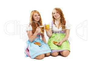 zwei frauen in dirndl mit brezeln und bier knien auf dem boden