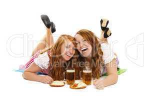zwei glückliche frauen in dirndl mit bier und brezeln liegen auf dem boden