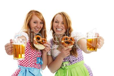 zwei frauen in dirndl mit brezeln zeigen bier