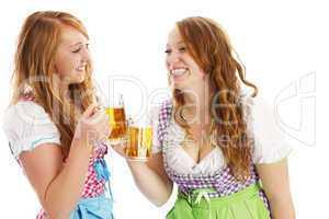 zwei glückliche frauen in dirndl beim anstossen mit bier