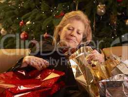 Müde ältere Frau mit vielen Geschenken