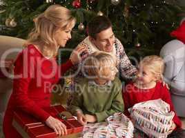 Glückliche Familie vor dem Christbaum