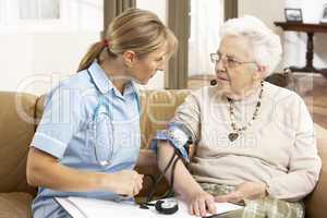 Senior Woman Ihaving Blood Pressure Taken By Health Visitor At H