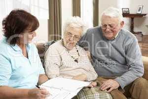 Senior Couple In Discussion With Health Visitor At Home