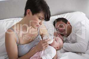 Mother Feeding Newborn Baby In Bed At Home