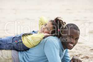 Father and daughter laying on beach