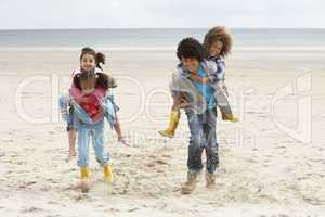 Happy children playing piggyback on beach
