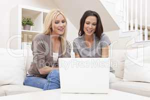Two Young Women Using Laptop Computer At Home on Sofa