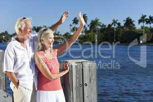 Happy Senior Couple Waving Outside in Sunshine by Sea