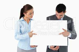 Business partners pointing at sign they are presenting