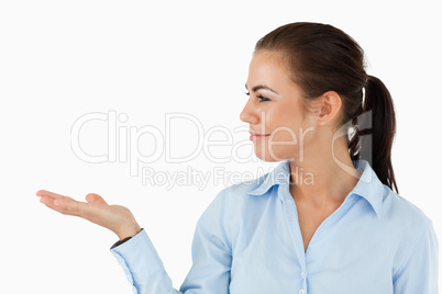 Businesswoman holding something up and looking at it
