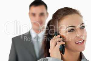 Close up of young businesswoman on the phone with colleague behi
