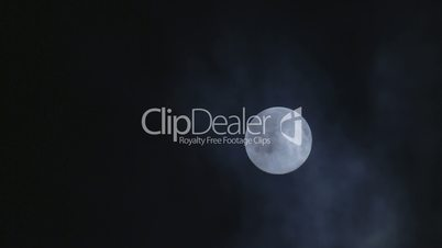 Full moon hiding by clouds on mist night sky background