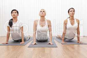 Interracial Group of Three Beautiful Women In Yoga Position