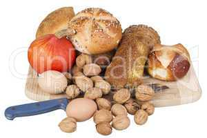 gem, nuts, eggs and a pumpkin on a wooden board