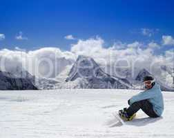 Snowboarder resting on the ski slope