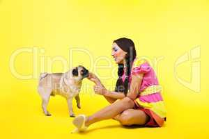 pin-up girl in doll dress feed a dog with cheese