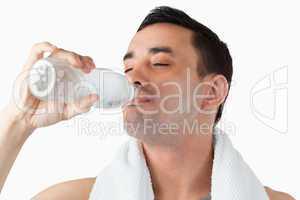 Young male enjoying a sip of water after workout