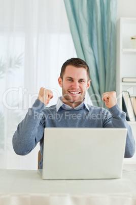 Businessman celebrating achievement in his homeoffice