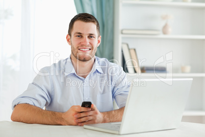 Young businessman typing text message in his homeoffice