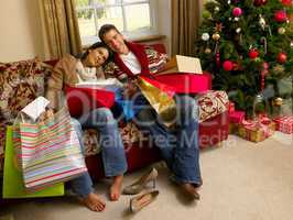 Young Hispanic couple resting after Christmas shopping
