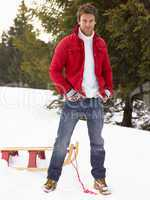Young Man With Sled In Alpine Snow Scene
