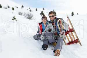 Young Father And Son In Snow With Sled