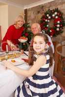 Child having Christmas dinner with grandparents