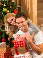 Young couple with gifts in front of Christmas tree
