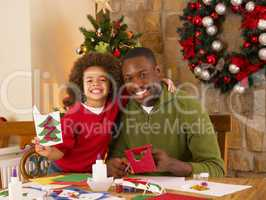 African American father and mixed race son making Christmas card