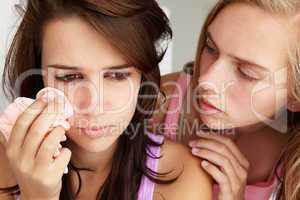 Teenage girl comforting tearful friend