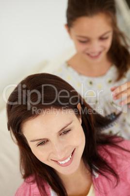 Girl brushing mother's hair