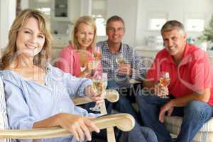 Mid age couples drinking together at home
