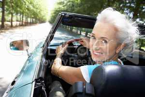 Senior woman in sports car