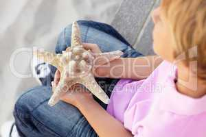 Young boy outdoors holding starfish