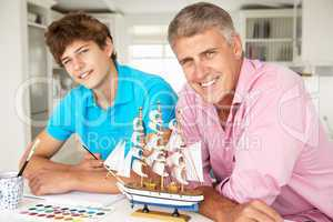 Father and teenage son model making and painting