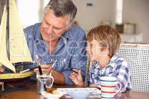 Senior man model making with grandson