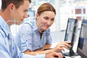 Businessman and woman working on computers