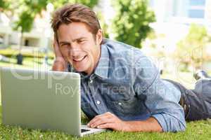 Man using laptop in city park