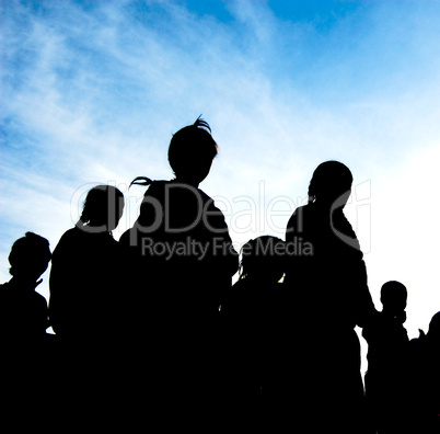 silhouette of family walking under the blue sky